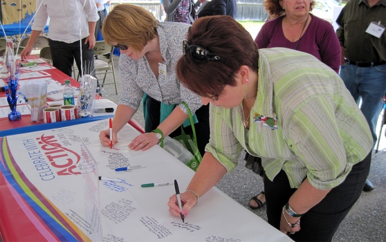 Photo of volunteers signing a petition at an advocacy event